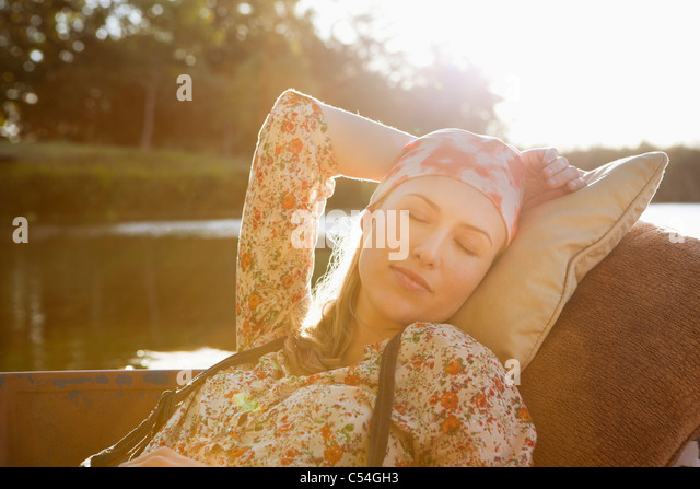 Beautiful woman sleeping in the boat - Stock Image