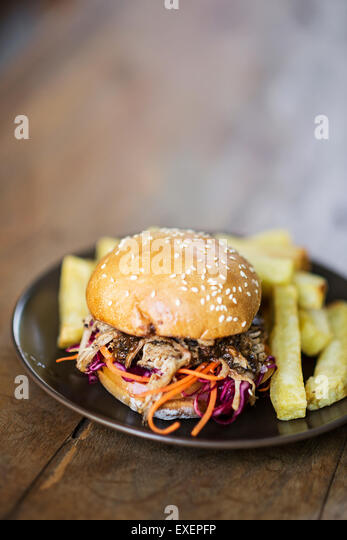 pulled pork and coleslaw burger with thick fries - Stock Image
