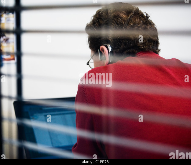 Man working in office, view from behind window blinds - Stock Image