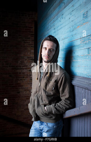 Man in hoodie in stairwell - Stock Image