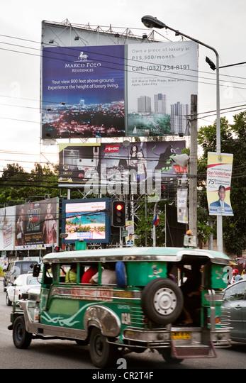 Jeepney driving past advertising billboards. Cebu City, Cebu, Visayas, Philippines. - Stock Image