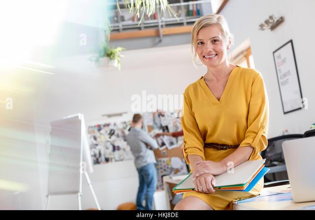 Portrait smiling female design professional leaning on office desk - Stock-Bilder