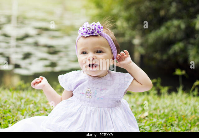 Close-Up Of A Cheerful Baby Girl On Grassland - Stock Image