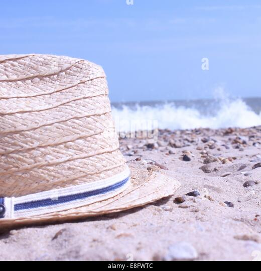 Close-up of a straw hat on beach - Stock Image