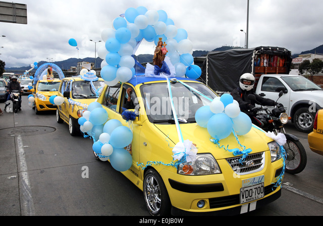 Parade of taxis decorated with balloons and statues of Mother Mary to honour the mother of Jesus Christ. Bogota, - Stock Image