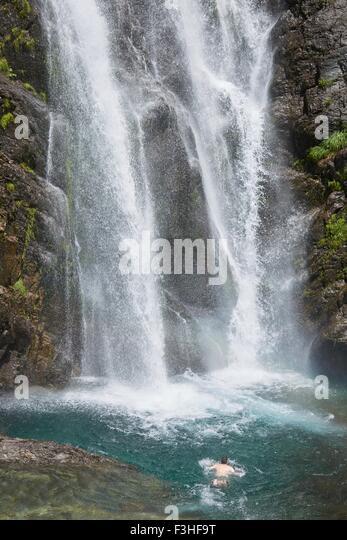 Man swimming near waterfall, Saut Deth Pish, Valle de Aran, Spain - Stock Image