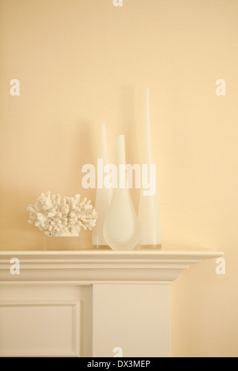 White vases and coral on mantel in living room - Stock Image
