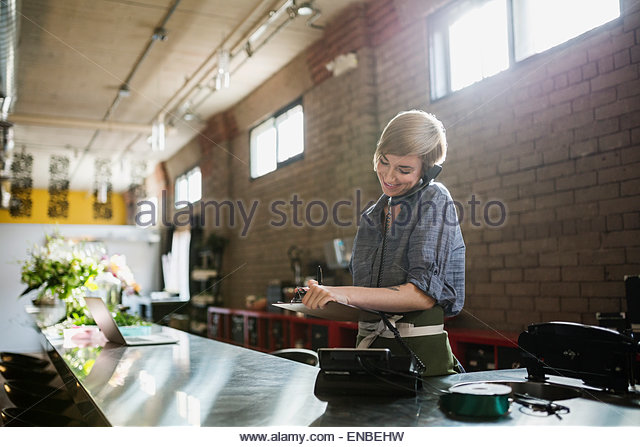 Florist taking order by phone in flower shop - Stock Image