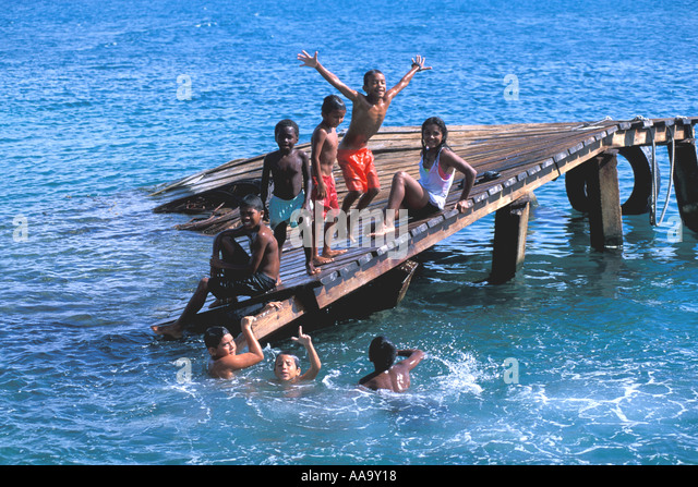 Honduras Bay Islands Guanaja Bohacca Island Children playing on old dock - Stock Image