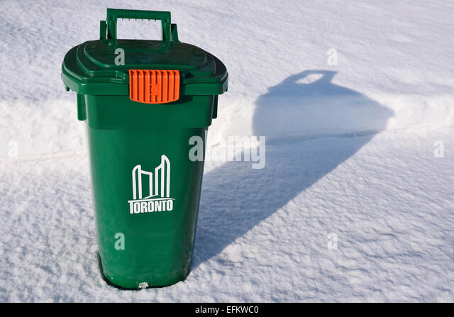 New Toronto green bin recycling on fresh snow covered sidewalk in winter - Stock Image