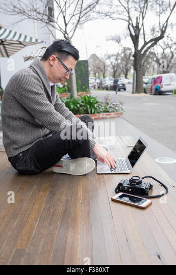 man on laptop working outdoors, with camera and phone - Stock Image