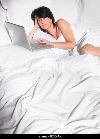 Woman in bed with computer - Stock-Bilder