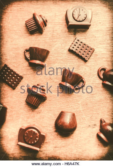 Coffee shop iconography with chocolate coffee cups and tea kettles on wooden cafe background - Stock Image