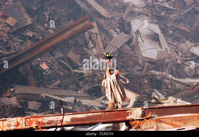 NYC Fire fighter carries a fire hose over smouldering fires and wreckage at Ground Zero, Sept. 18, 2001. World Trade - Stock-Bilder