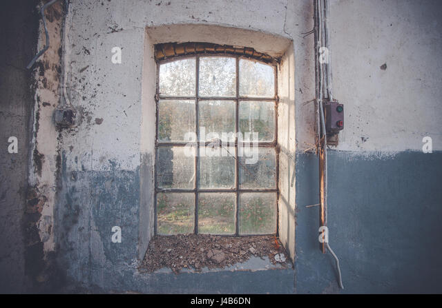 Dirty old window on a grunge wall with cracks and pealing blue paint with an electrical switch beside - Stock Image