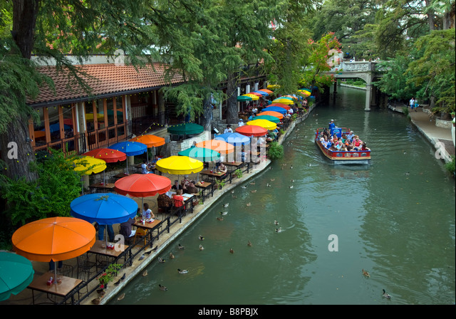 San Antonio River Walk riverwalk row of blue yellow orange umbrellas of outdoor cafes line river bank - Stock Image