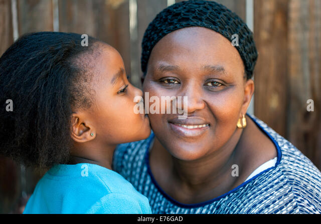 Close up portrait of little girl kissing mother on cheek outdoors. - Stock Image
