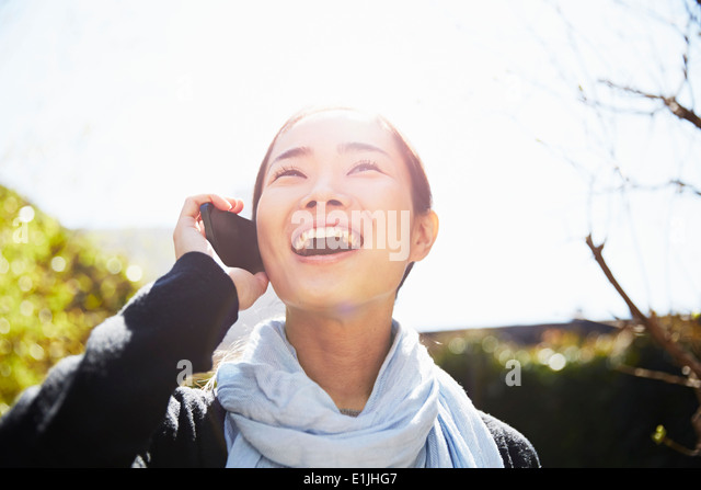 Young woman on smartphone, laughing - Stock-Bilder