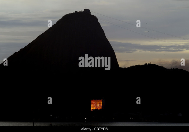Building is illuminated by the golden rays of the sun and Sugarloaf one of the big attraction in Rio in the distance - Stock Image