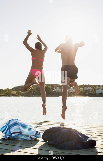Full length rear view of couple diving into lake - Stock Image