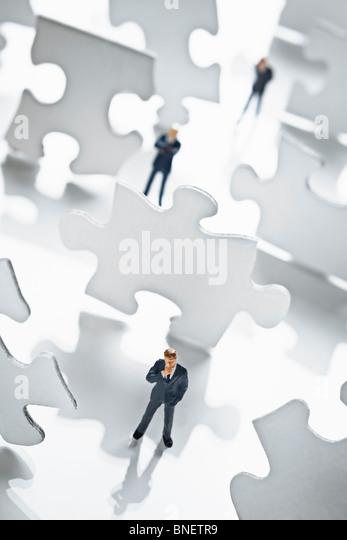 Businessman figurine surrounded by puzzle pieces - Stock-Bilder