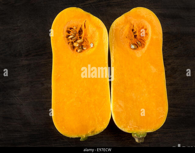One butternut squash cut in halves on a dark background - Stock Image