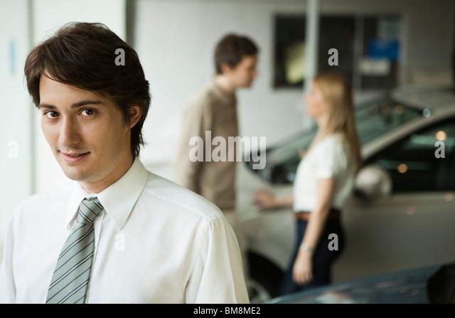 Car salesman in dealership showroom, potential buyers in background - Stock Image
