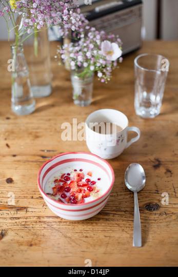Bowl of fruit and yogurt with coffee - Stock Image