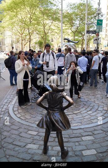 Fearless girl sculpture facing charging bull New York City public art bowling green broadway USA - Stock Image