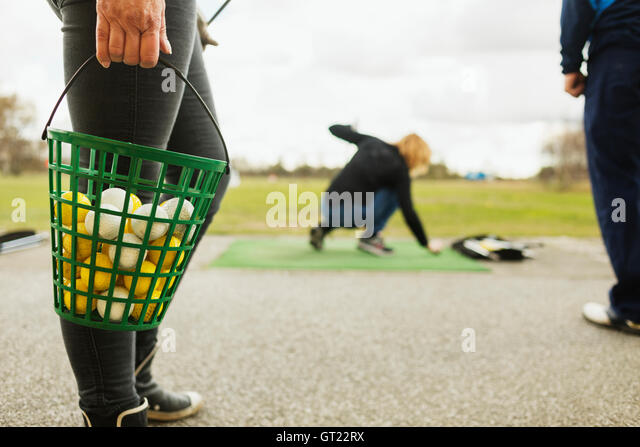 Low section of woman holding basket with balls at golf course - Stock-Bilder