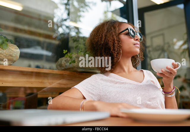 Portrait of attractive young african girl having a cup of coffee at cafe. Stylish young girl drinking coffee at - Stock Image