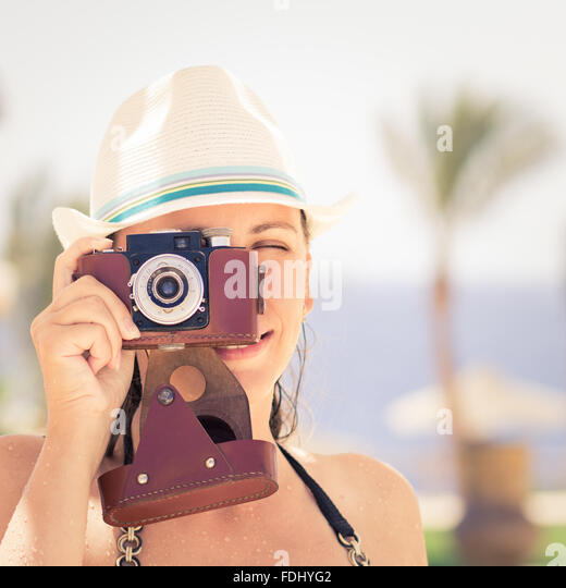Young happy woman having fun with old photo camera at the summer beach holidays. - Stock-Bilder