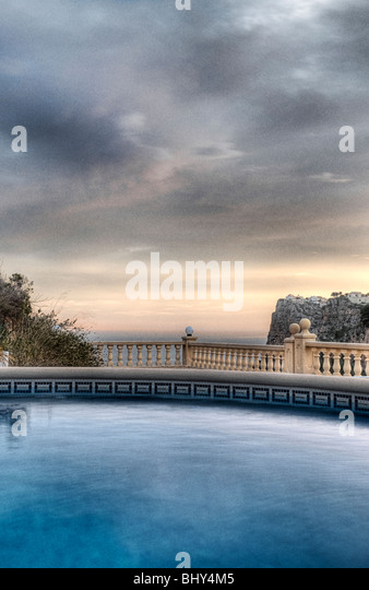 Beautiful Shot Over a Luxury Swimming Pool onto the Mediterranean Sea in Spain - Stock Image