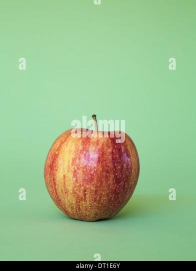 Honey Crisp apple on green background - Stock Image