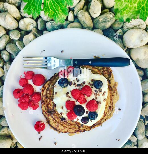 Banana Pancakes with Greek Yogurt, Raspberries, Blueberries & Cacao Nibs - Stock-Bilder