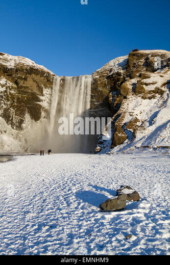 Tourists admire the Skogafoss waterfall in Iceland during the short winter day - Stock Image