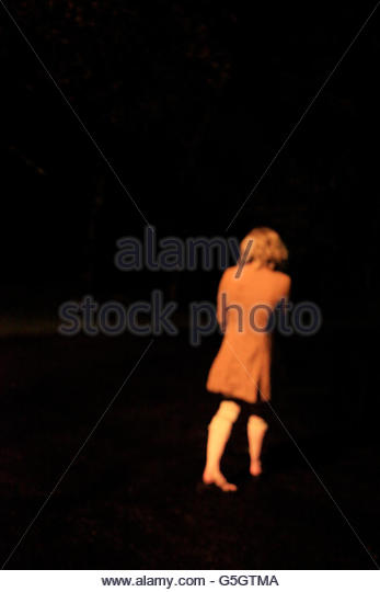 Girl walking alone on road at night time.lit street lights. - Stock-Bilder