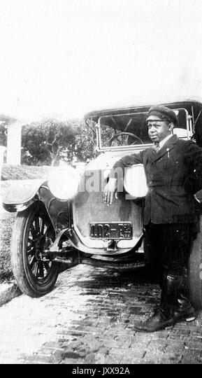 Full length portrait of an African American man leaning against headlights of a car, wearing chauffeur's uniform, - Stock Image