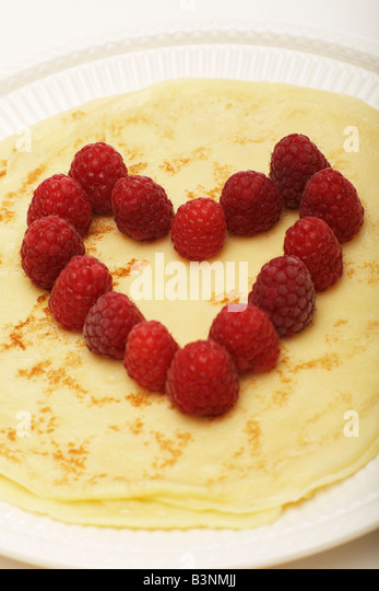Pancake with raspberries, heart shaped, close-up - Stock Image