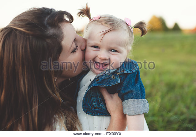 Mother kissing baby daughter on cheek, outdoors - Stock Image
