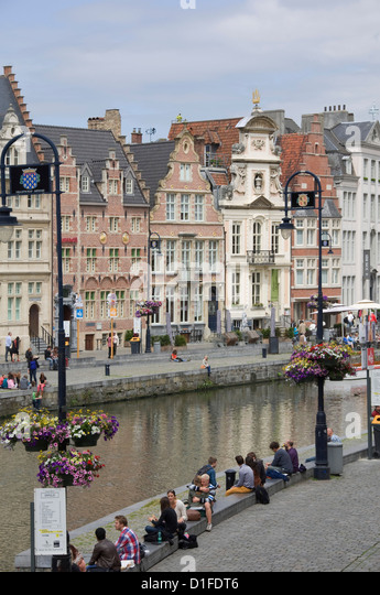 Students relaxing along the banks of the Graslei, Baroque style Flemish gables in the background, Ghent, Belgium, - Stock-Bilder