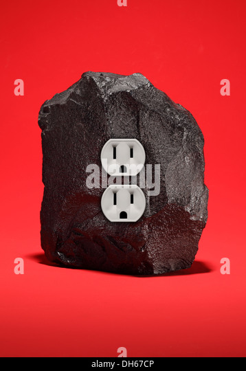 A large piece of black coal with an double electrical outlet. Bright red background - Stock Image