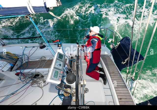The captain steering an Ocean going yacht in race on choppy ocean waves. - Stock-Bilder