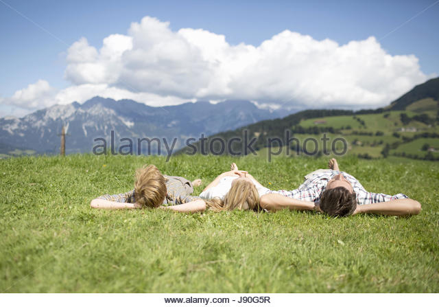 Father And Children Lying On Backs In Summer Field - Stock-Bilder