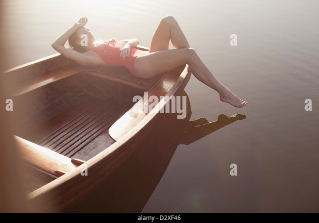 Serene woman sunbathing in boat on lake - Stock Image