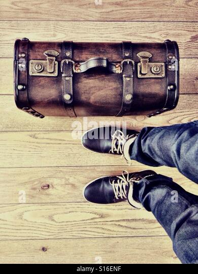 Man wearing brown leather shoes is standing on a wooden floor next to a brown nostalgic suitcase - Stock Image