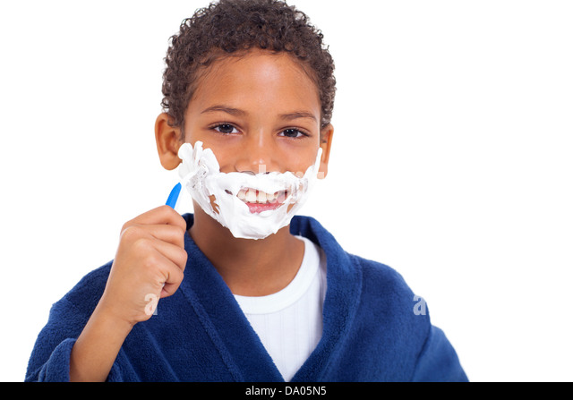 playful little african young boy shaving face over white background - Stock Image