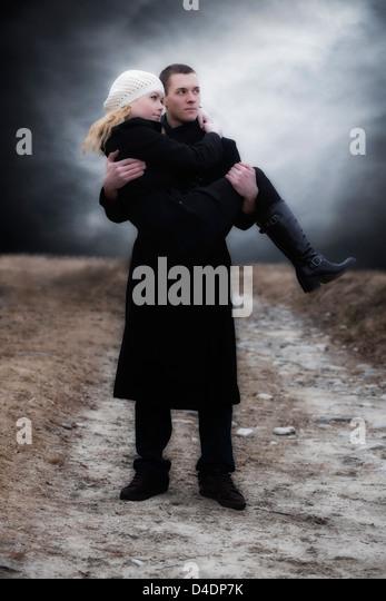 a man carries his girlfriend over a meadow - Stock-Bilder
