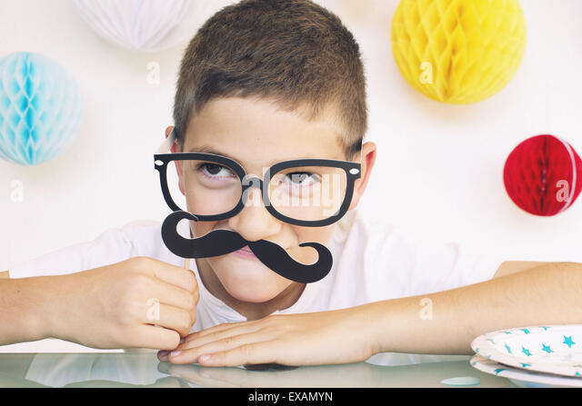 Boy wearing fake glasses and mustache at a birthday party, portrait - Stock Image