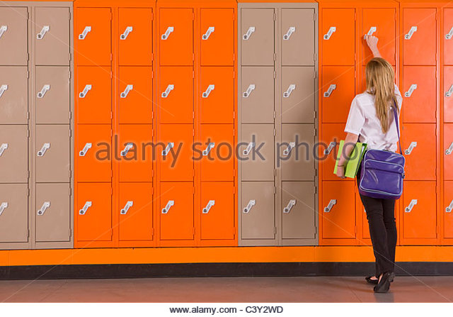 Student unlocking school locker - Stock Image